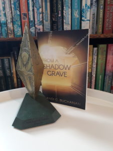 Photo showing a paperback copy of Andi C. Buchanan's FROM A SHADOW GRAVE next to a Sir Julius Vogel Award trophy.