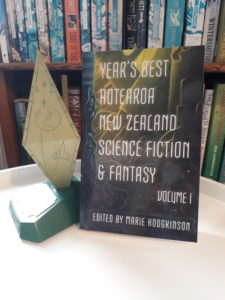 Photo showing a paperback copy of YEAR'S BEST AOTEAROA NEW ZEALAND SCIENCE FICTION AND FANTASY, Volume 1, edited by Marie Hodgkinson, next to a Sir Julius Vogel Award trophy.